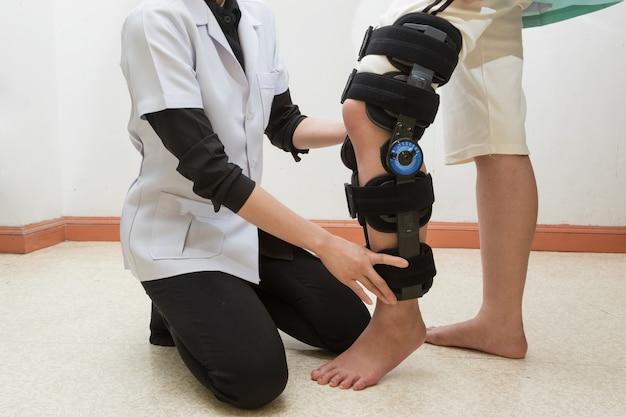 Fisioterapia femenina que ajusta el apoyo de caminata en la pierna del paciente en clínica