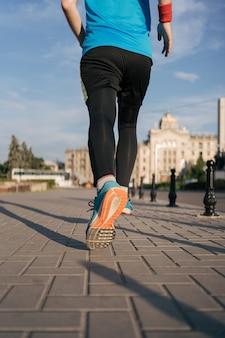 Fit hombre corriendo piernas en la ciudad