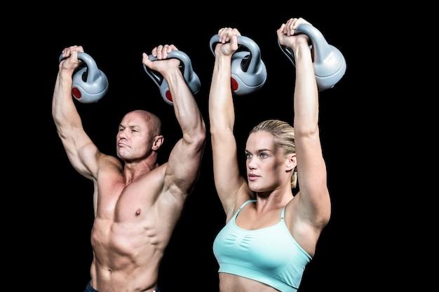 Fit hombre y mujer levantando kettlebells