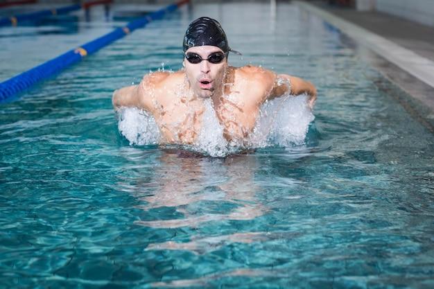 Fit hombre nadando en la piscina