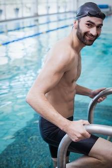 Fit hombre saliendo del agua en la piscina