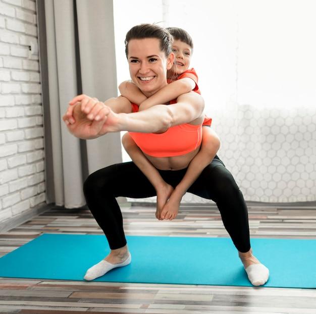 Fit madre haciendo ejercicio junto con hijo