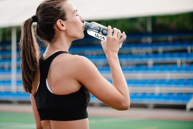 Fit mujer agua potable durante el entrenamiento deportivo en el estadio