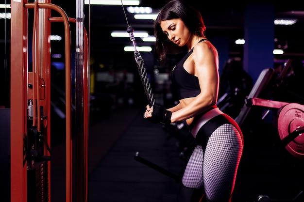 Fit mujer entrenamiento tríceps levantando pesas en el gimnasio