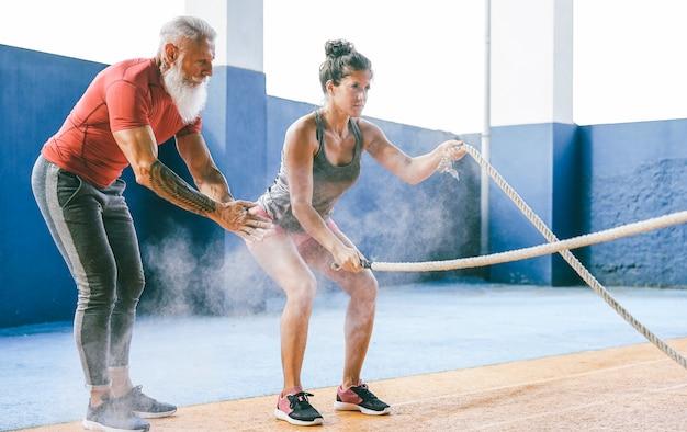 Fit mujer entrenando con cuerda de batalla dentro del gimnasio