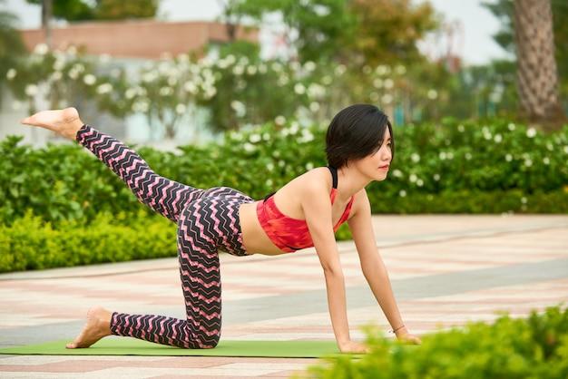Fit mujer entrenando en estera de yoga