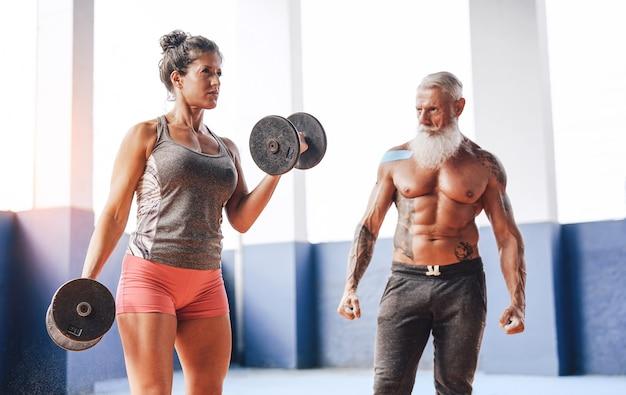 Fit mujer haciendo ejercicios de bíceps curl con pesas en el gimnasio gimnasio