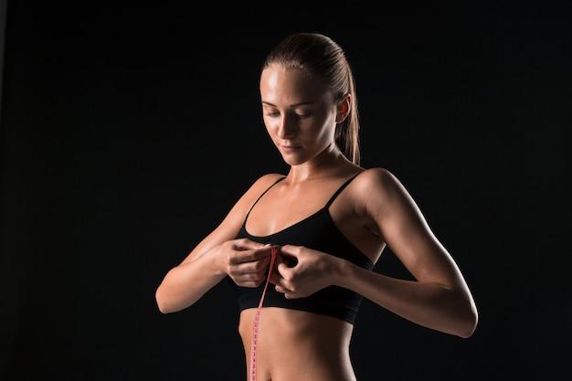 Fit mujer midiendo la forma perfecta del cuerpo hermoso