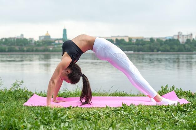 Fit mujer practicando yoga al aire libre urdhva dhanurasana pose de arco hacia arriba ejercicio de asana.