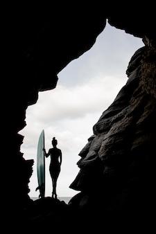 Fit mujer con tabla de surf de pie entre las rocas