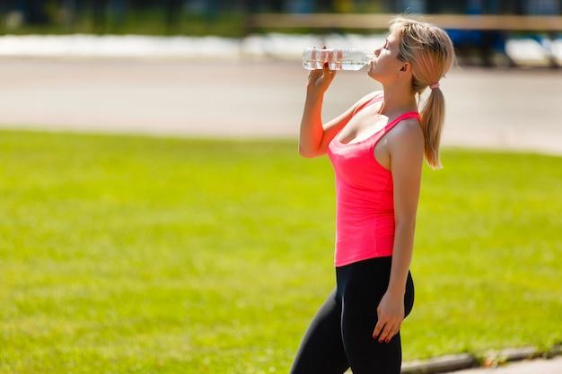 Fitness atleta mujer beber agua fresca y descansar después de un duro entrenamiento