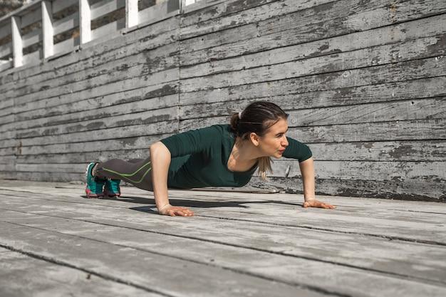 Fitness chica deportiva en ropa deportiva está haciendo ejercicios sobre un fondo de madera, fondo claro, el concepto de deportes