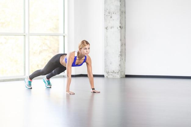 Fitness, concepto de deporte. mujer en interior de loft haciendo push up. foto de estudio, aislado sobre fondo gris