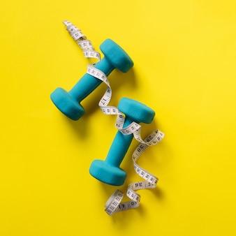 Fitness, concepto de deporte con pesas y cinta métrica sobre fondo amarillo