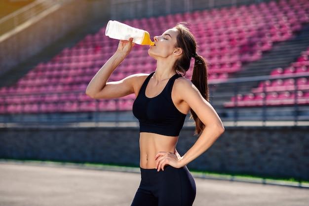 Fitness corredor mujer beber agua o bebida energética de una botella deportiva