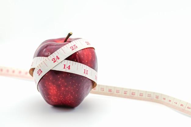 Fitness y cuidado de la salud concepto. cerca de manzanas con cinta métrica