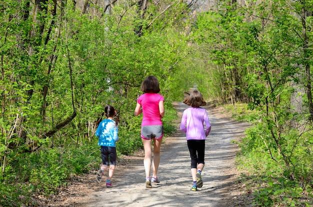 Fitness y deporte familiar, feliz madre activa y niños corriendo al aire libre, corriendo en el bosque