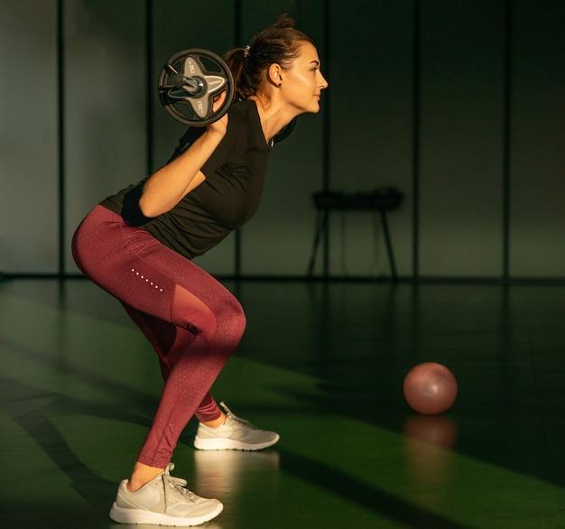 Fitness, deporte, levantamiento de pesas y concepto de personas - mujer deportiva haciendo ejercicio con barra en el gimnasio