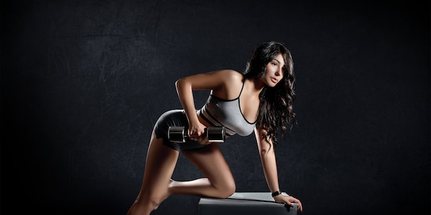 Fitness deportes mujer entrena sobre un fondo oscuro