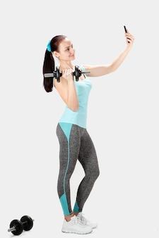 Fitness deportes mujer sosteniendo pesas y tomar selfie