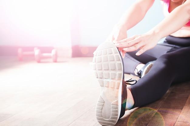 Fitness femenina en pantalones negros y zapatillas de deporte que se extiende después del entrenamiento con espacio de copia