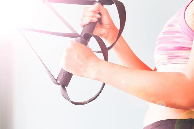 Fitness femenina en sujetador de deporte rosa con las manos en trx, copiar el espacio
