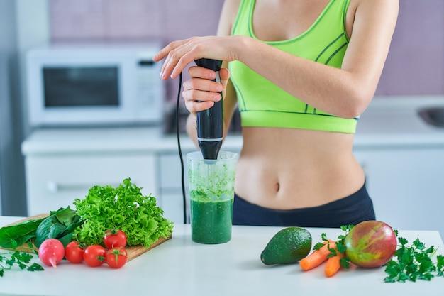 Fitness femenino en ropa deportiva prepara un batido verde con una batidora de mano en la cocina.