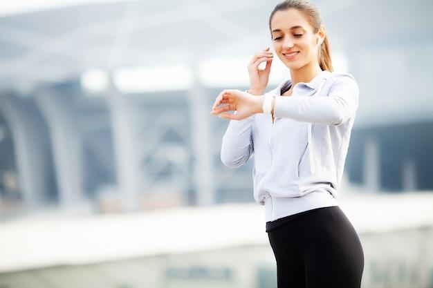 Fitness hermosa mujer agua potable y escuchar música después de correr
