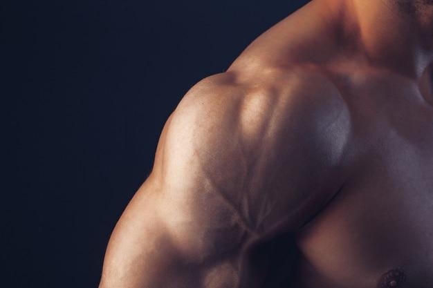 Fitness hombre fondo bíceps hombro músculos pectorales tríceps culturista sobre un fondo oscuro muestra la forma física para las clases en el gimnasio