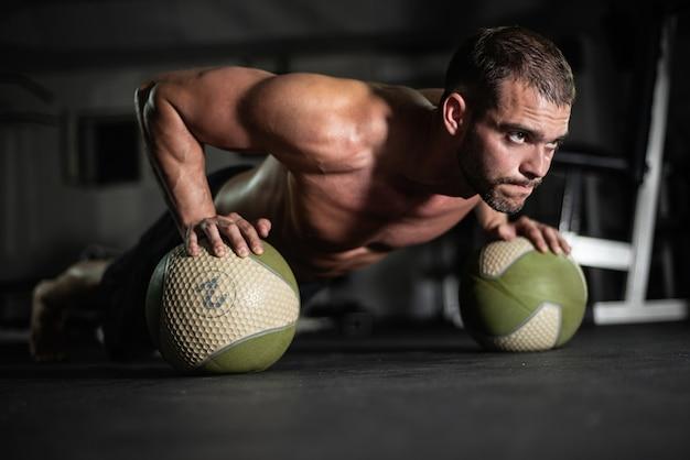 Fitness hombre hace flexiones en las bolas.