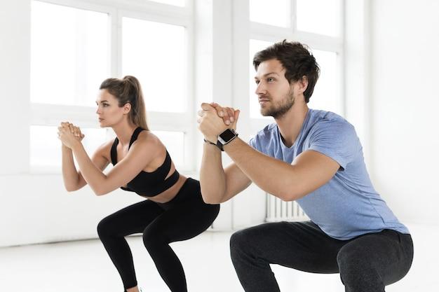 Fitness hombre y mujer durante el entrenamiento en el gimnasio. ejercicio de sentadillas para glúteos y caderas.
