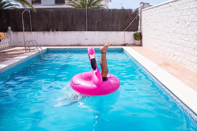 Fitness hombre saltando al agua en la piscina en el centro del flamenco inflable un día de vacaciones de verano