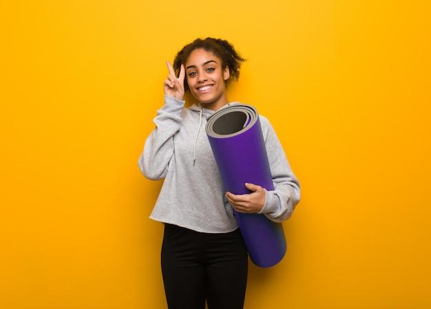 Fitness joven mujer negra divertida y feliz haciendo un gesto de victoria. sosteniendo una estera.