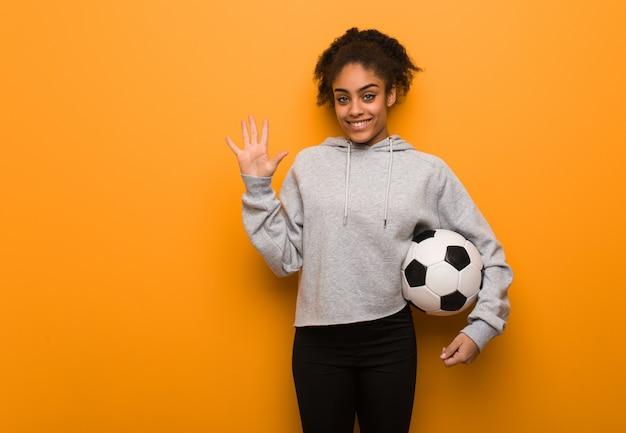 Fitness joven mujer negra mostrando el número cinco. sosteniendo un balón de fútbol.