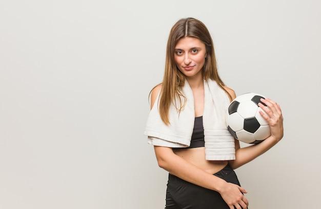 Fitness joven mujer rusa cruzando los brazos, sonriente y relajado sosteniendo un balón de fútbol