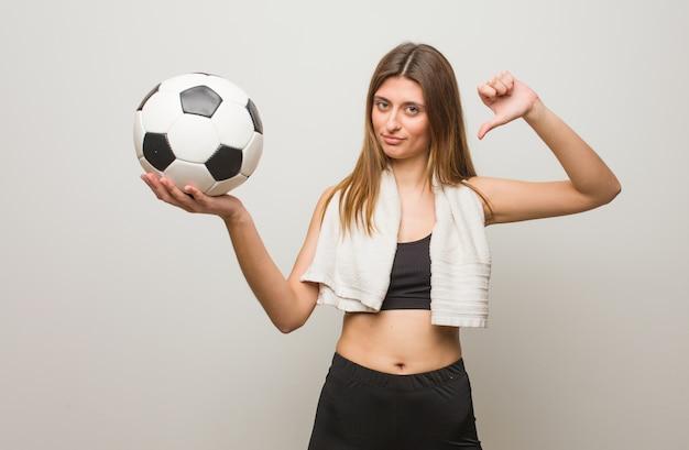 Fitness joven mujer rusa señalando con el dedo, ejemplo a seguir. sosteniendo un balón de fútbol.
