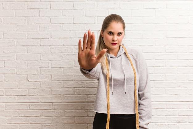 Fitness joven mujer rusa sosteniendo una cinta métrica