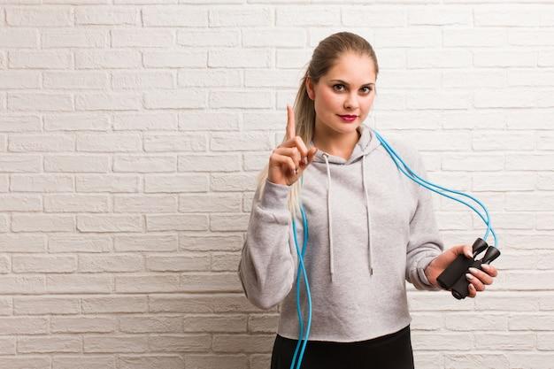 Fitness joven mujer rusa sosteniendo una cuerda de saltar contra una pared de ladrillos