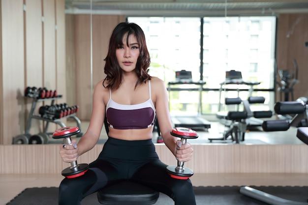 Fitness mujer asiática levantando pesas y entrenamiento en gimnasio con cara bonita