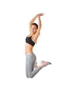 Fitness mujer asiática saltando sobre blanco