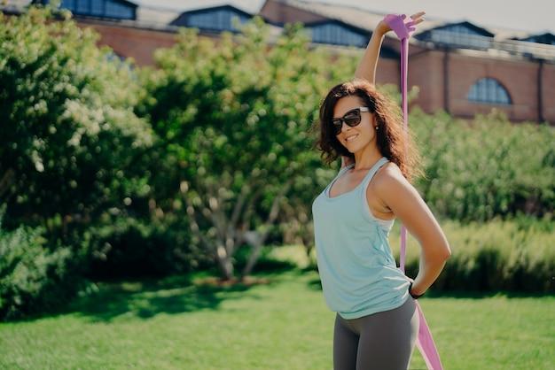 Fitness mujer atlética hace ejercicio con banda elástica vestida con ropa deportiva gafas de sol de moda plantea fuera
