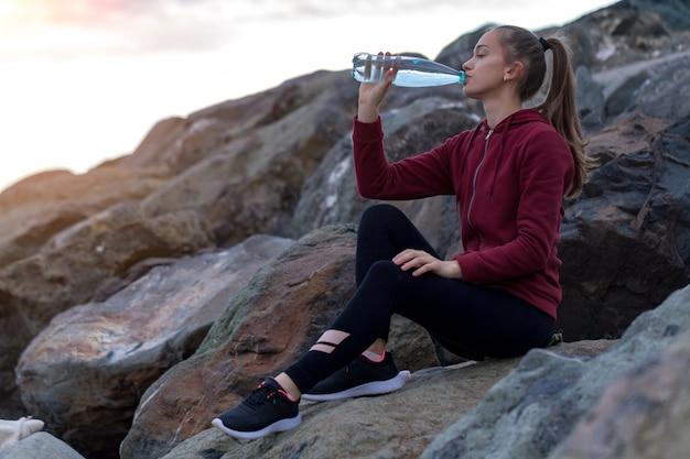 Fitness mujer atractiva en zapatillas sentado en una piedra