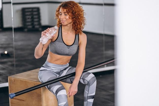 Fitness mujer bebiendo agua de botella en el gimnasio