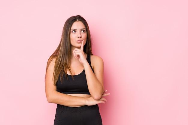 Fitness mujer caucásica joven mirando hacia los lados con expresión dudosa y escéptica.