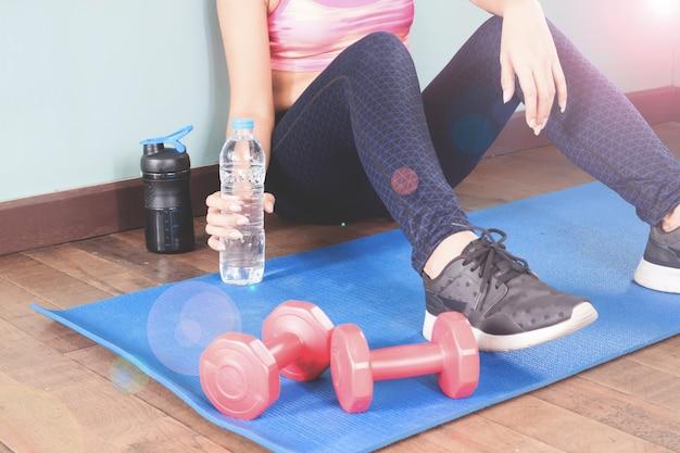 Fitness mujer celebración botella de agua después del entrenamiento, concepto de estilo de vida saludable