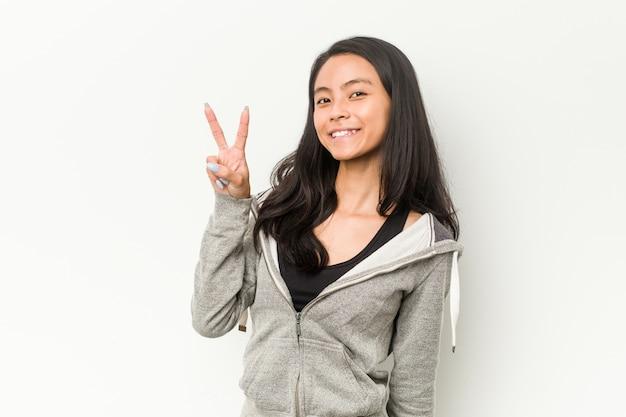 Fitness mujer china joven alegre y despreocupada mostrando un símbolo de paz con los dedos.