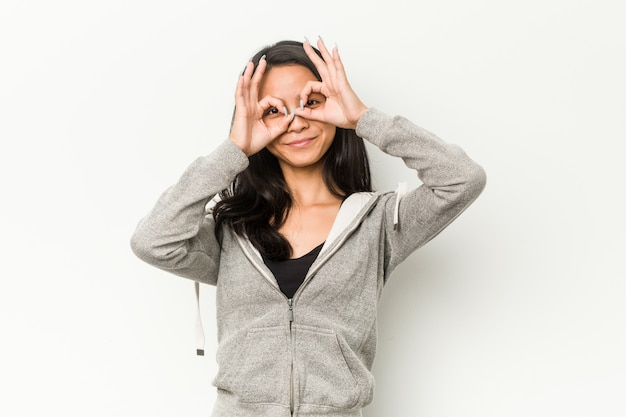 Fitness mujer china joven que muestra bien firmar sobre los ojos