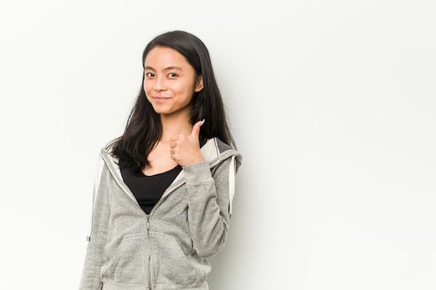 Fitness mujer china joven sonriendo y levantando el pulgar hacia arriba