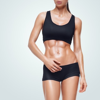 Fitness mujer deportiva caminando. se muestran abdominales fuertes.