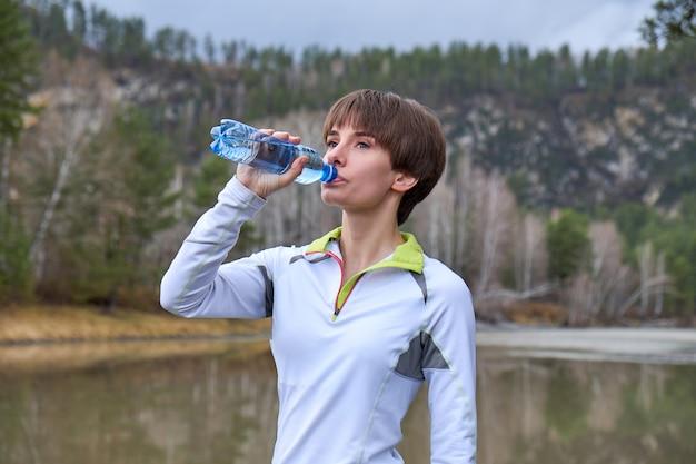 Fitness mujer es beber agua de una botella en una naturaleza. retrato de deportes al aire libre